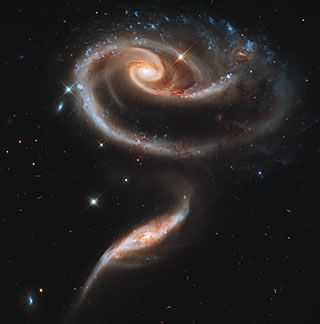This image of a pair of interacting galaxies called Arp 273 was released to celebrate the 21st anniversary of the launch of the NASA/ESA Hubble Space Telescope.  The distorted shape of the larger of the two galaxies shows signs of tidal interactions with the smaller of the two. It is thought that the smaller galaxy has actually passed through the larger one