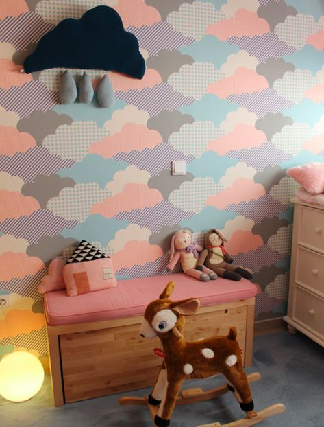 A nursery with colorful wallpaper.