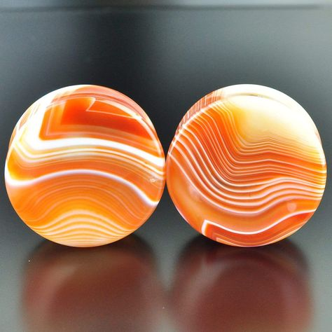 Purchase this exact set. No questions as to what the pair you select will look like, the photo provided is the exact set you will receive! Red Banded Agate – Also called sardonyx, this beautiful stone is a common variety of chalcedony and can vary in color from orange to red with white to clear banding. They have been heat treated to enhance the color intensity. We have hand selected some of the most beautiful stone available and crafted into beautiful plug sets for your enjoyment. Every set is  Tapers And Plugs, Stone Plugs, Pokemon, Fancy Houses, Heat Treating, Tunnels And Plugs, Ear Gauges, Red Band, Rocks And Gems