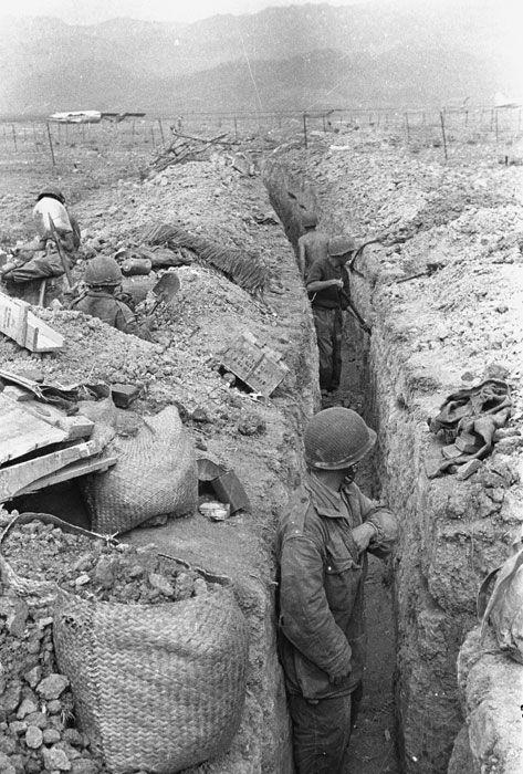 Aux abords immédiats de la piste d'atterrissage du camp retranché de Diên Biên Phu, les parachutistes renforcent la position dans les tranchées tenues par le 8e BPC (Bataillon de Parachutistes de Choc). Date : Mars 1954