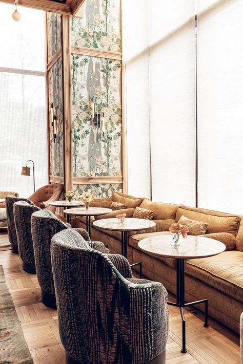Kelly Wearstler Restaurants  Bars Design • Goldie's • With a color palette reflective of a feminine vibe, accented with feminine touches like desert rose marble tables, Goldie's is a bar lounge in the Austin Proper Hotel that is both inviting and alluring. Original printed linen fabric inspired by the golden warbler bird upholsters the walls alongside millwork crafted from local timber, encasing the sunken bar. #kellywearstler #interiordesign #designer