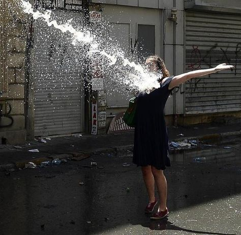 #occupygezi young woman in Istanbul welcoming a stream of water canon with open arms.