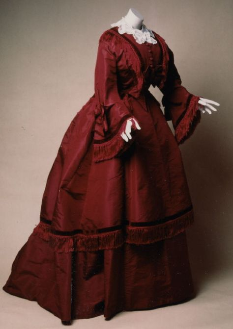 Woman's wedding or afternoon dress: bodice, skirt, and cape Date: ca. 1860 Media: Silk Rep, Silk Fringe, Velvet Ribbon, And Embroidered Lace Accession Number: 48.20.1a-c Burgundy 3-piece dress:fitted boned bodice, full-length underskirt and shorter overskirt. Sleeves flare from elbow bow. High neckline trimmed with detatchable lace collar. Fringe and velvet ribbon trim bodice front, sleeve hems and hem of overskirt.