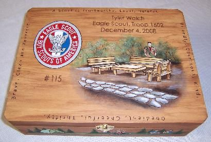 An Eagle Scouts project is painted on top of the box with his name troop and date of his Eagle ceremony. Painted around the sides are his favorite activities. Inscription to the Scout written inside the lid. Measures 12