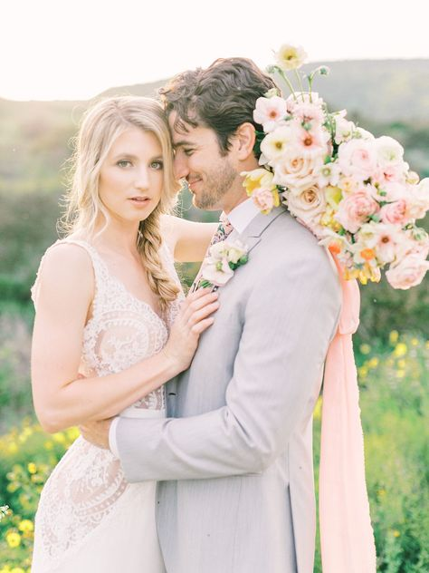 This beautiful wedding bouquet is packed full with all the best spring time flowers daffodils, lilac, tulips, butterfly ranunculus, etc. with a fun vibrant and playful color palette paired with pink silk ribbon. The colors pop of the green hills of Mission Trails in San Diego, California during the Super Bloom. #sandiegoweddingflorist #sandiegowedding #sandiegoweddingflowers #sandiegoflorist #springweddingbouquet #springbouquet #daffodilbouquet #lilacbouquet