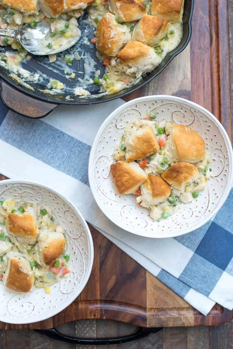 A creamy, chicken and vegetable studded filling is topped with biscuit pieces and baked until bubbly and golden brown. This family-friendly Skillet Chicken and Biscuit Pot Pie is an easy, comforting weeknight dinner choice. #potpie #chickenpotpie #easyrecipes #onepot #onepotrecipes #comfortfood