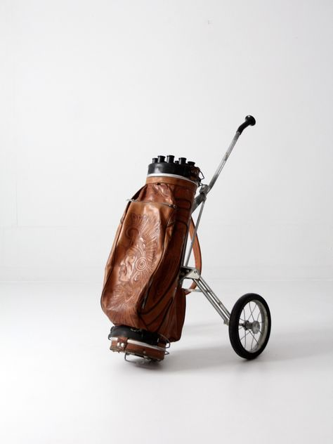 circa A vintage tooled leather golf club bag with a vintage Ajay Playmate cart. The caramel leather bag features an Indian chief design. It features three pockets and a leather carrying strap.