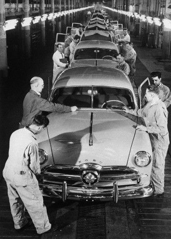 Workers put the finishing touches on a 1949 Ford sedan.