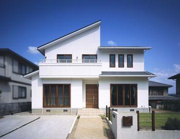 青空に映える白い外壁に ブラウンの木製玄関ドアや木調サッシが