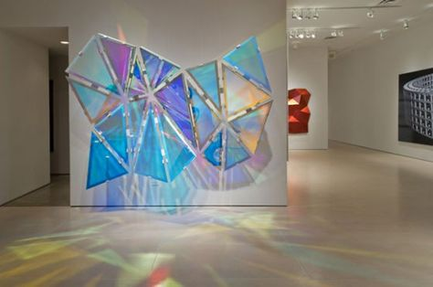 Eckart's dichroic glass triangles shift in color as you move past.