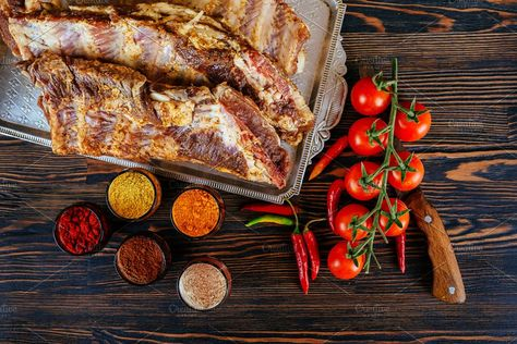 raw marinated pork ribs and tomatoes of garlic pepper on a black board Raw fresh meat and vegetable on wooden background.