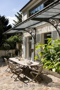 The terrace beside the outdoor swimming pool is furnished with a combination of white bamboo side tables and pink wrought iron tables and chairs & Gotta find a place to use the beautiful old wrought iron awning ...