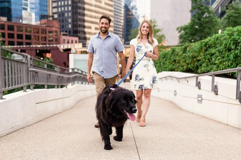 Happy couple and happy dog walk along river during downtown Chicago engagement session