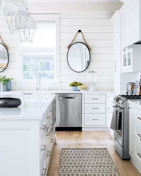 White panel walls, light hardwood floors and white cabinets and countertops in this kitchen design | Lidia van Zyl Design
