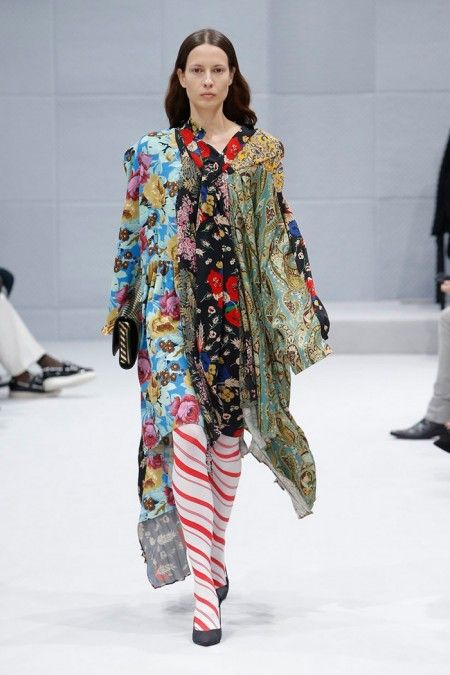 A model walks the runway at Balenciaga's fall-winter 2016 show wearing a multi-print dress with candy striped stockings