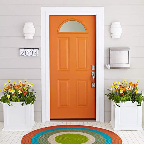 "A cheerful orange door, particularly sharp next to light gray siding and white trim. This one says ""A fun person will be found inside!"""