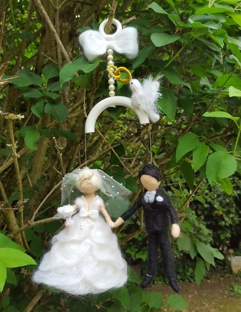 Decoration for the best day, marriage ... Mobile painted wood ring for hanging, large knot carded wool, beads and feather dove with wings holding alliances. The bride: Ruffle Dress with a neckline beads. On the head, crown on a tulle veil sprinkled with pearls, rose bouquet in hand.