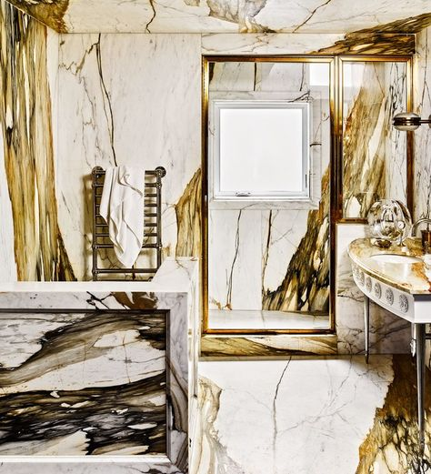The master bath is clad in Calacatta gold marble. Sink fittings by Kallista, towel warmer by Ferguson, and vintage sconce by Sergio Mazza.