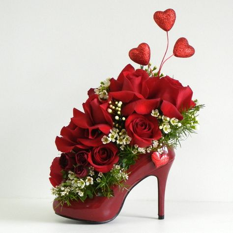 """shoe flower arrangement~~~ very cute for a """"girls"""" luncheon or shower. Did these for a bridal shower with the title of """"The Shoe Fits, Holly Has Found Her Prince"""".Did a different shoe for each table. Place plastic in shoe and then place a oasis and fill."""