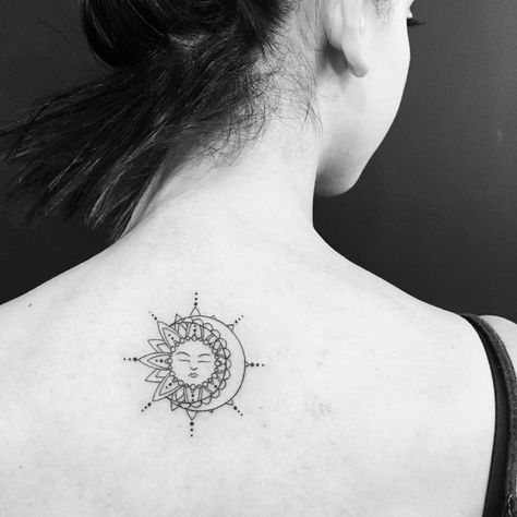 Sun and moon tattoo on the upper back.