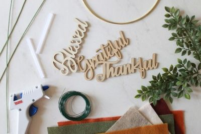 Items from a Craftee DIY subscription box, including a hot glue gun, green wire, various colors of felt, and wooden words.