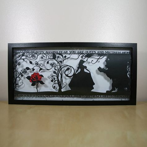 A beautiful hand cut papercut depicting a scene from Beauty and the Beast with a translated quote from the Brothers Grimm version of the tale.