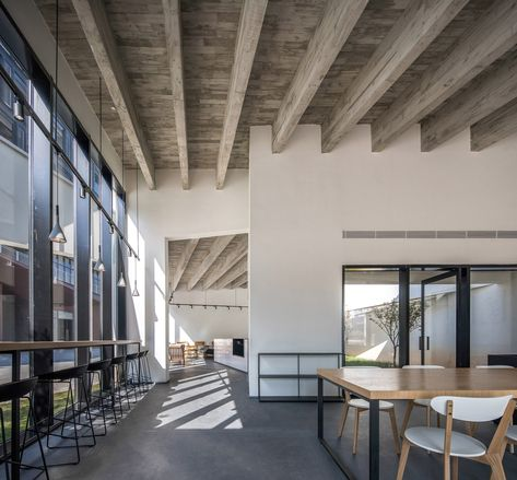 Unfinished Concrete Beams Running From East To West Emphasise The Sloping Rooflines Inside The Buildi In 2020 Concrete Interiors Interlocking Concrete Blocks Architect