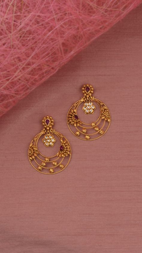 Delicate crescent hoop earrings with ornamental floral accents.