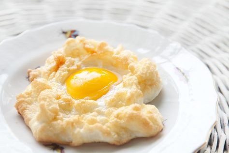 Egg whites whipped to stiff peaks, grated Gruyere folded in, formed into nests, baked with yolk in center.