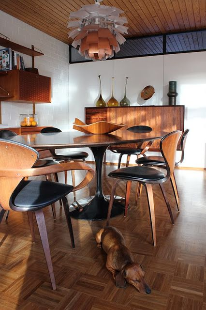 Olive Green Window - Tulip table with teak top and black base, Cherner chairs and a PH Artichoke lamp. And Daschund