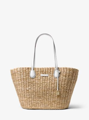 57aaed3f9 Destined for your next island escape, our Malibu tote is woven from natural  straw with leather handles and our signature lock charm.