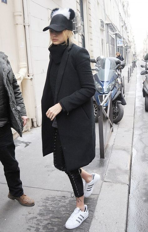 Gigi Hadid wears a turtleneck sweater, black coat, lace-up leggings, Adidas sneakers, and a pom-pom cap