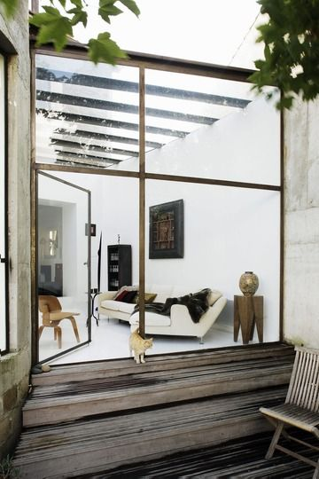 Open living room, glass windows, cat, white couches, wooden stairs, trees, sculpture