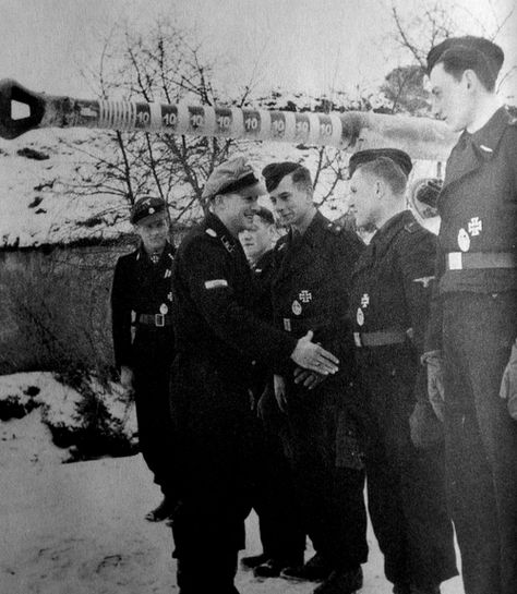 Renowned Tiger ace Michael Wittmann (left) presenting his crew to his SS superior Joachim Peiper (later of Malmedy massacre fame) on the Eastern Front, 18 January 1944. In June Wittman achieved an astonishing single handed success against the British at Villers-Bocage, but was killed in combat by one of their Sherman Fireflys in August.