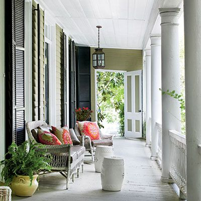 Classic Charleston Porch with wicker, bright pillows and ceramic garden seats via Southern Living. #porch