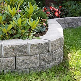 A-cemented retaining wall made with stone pavers