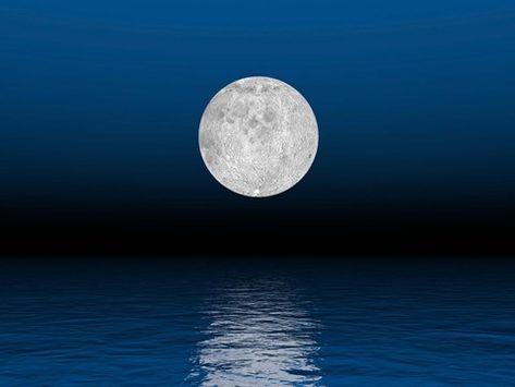 Elena Duvernay/Stocktrek Images Beautiful full moon against a deep blue sky  over the ocean