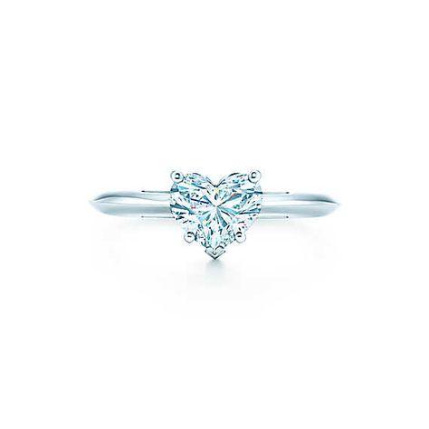 Serti sur platine, ce diamant en forme de cœur est orné du symbole classique de l'amour.