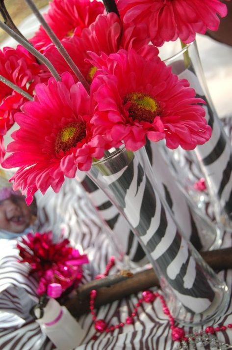 Hot pink silk Gerber daisies and clear vases lined with zebra print scrapbook paper for a baby girl shower!
