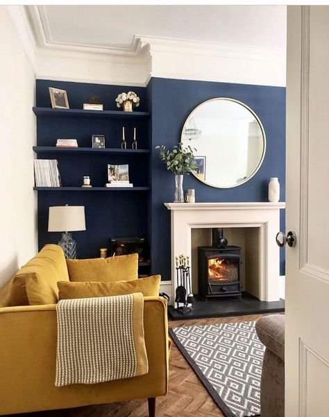 Living room in Victorian terrace house navy blue and yellow with fireplace
