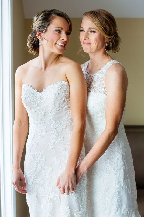 Wedding day photo of the brides in their wedding dresses at lakefront wedding venue | Photo: Michelle Arlotta