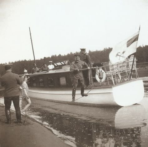 "Tsarevich standing on land by the boat which transported passengers to the Imperial Yacht the ""Standart"""