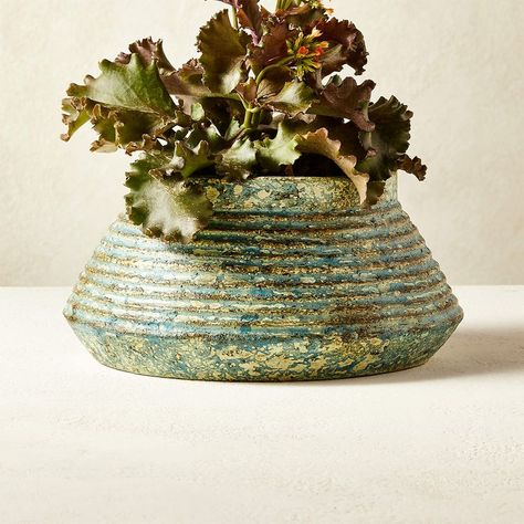 This unique, low planter gets its linear, angled design from being shaped in a mold and then dried in the sun. Once the piece is fully dried, it's fired, then painted with a reactive glaze and fired again. The coloring process is done by hand, so each piece will vary a little in color, tone and texture. CB2 exclusive.