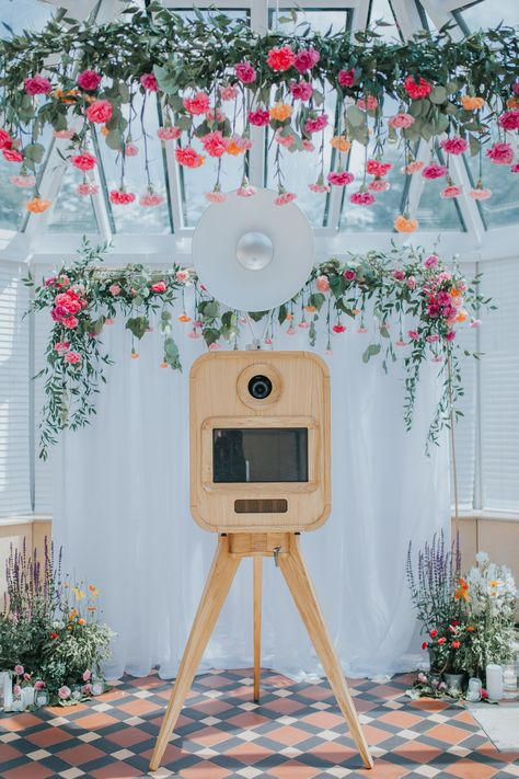 Pink and orange carnations added a pop of color to this white photo booth backdrop by Viva La Booth.
