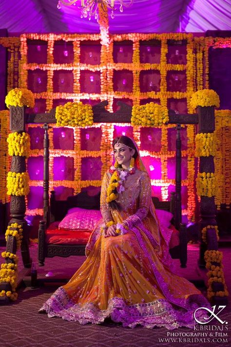 Hindustani mehndi ceremony. The bride is perched upon a wooden swing atop the raised dais while her friends and family make their way up to her to smear henna on her hands and offer their blessings to the bride and groom. Traditionally, bridal dress and decor is yellow.