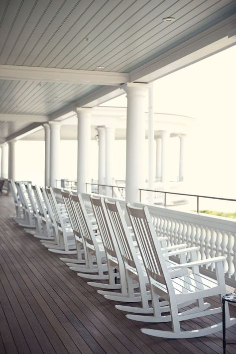 A porch outfitted with enough rocking chairs for the whole family