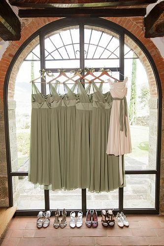 Bridesmaide dresses hanging in a window with a view- Villa Il Fienile. Sage green, ivory and touches of peach & pink. Ideas for Tuscan wedding colors. @thebuccellettifamilyestate #tuscanwedding #softcolors #weddingsintuscany
