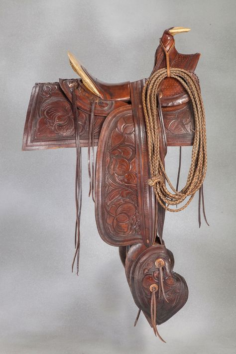 """Wonderful early trail saddle with California influence. Large leaf tooling and swept-back lower skirts. True half-seat with Sam Stagg rigging and exposed upper cantle. 12 ½"""" seat, 4 ½"""" cantle. 4 per side copper slotted conchos, riveted stirrup leathers, no side jockeys, exposed rawhide horn. 14 ½"""" tapaderos have 4 slotted copper conchos each. With period rawhide reata. A true showpiece and premiere example of an early California ranching saddle. Circa 1860-"""