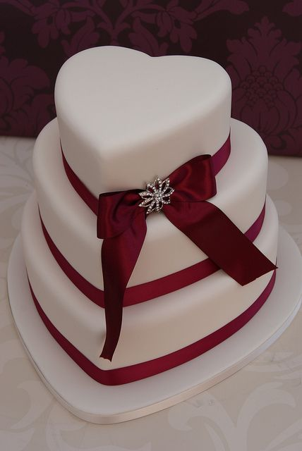 Like the layered cake and the red ribbon. Will look nice with squared patterns maybe with white gems in middle. Cake topper and some red roses petals/roses? Different pin on the ribbon
