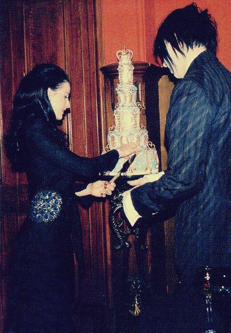 Manson and Dita cutting their wedding cake.